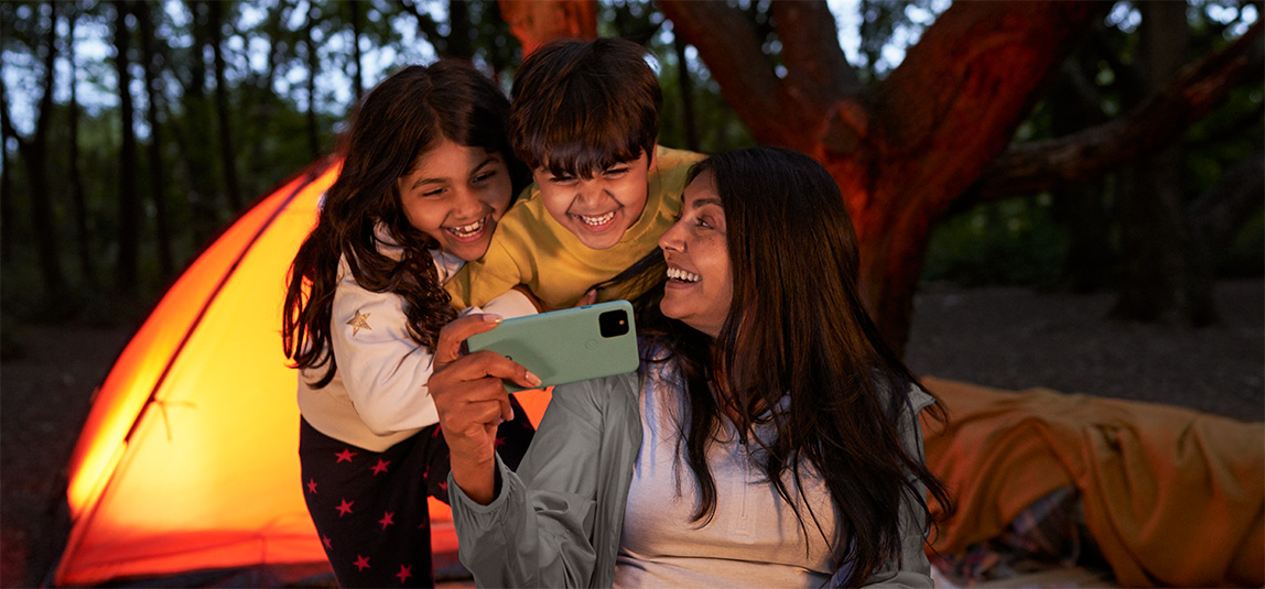 Image of a mom showing her two kids something funny on her phone