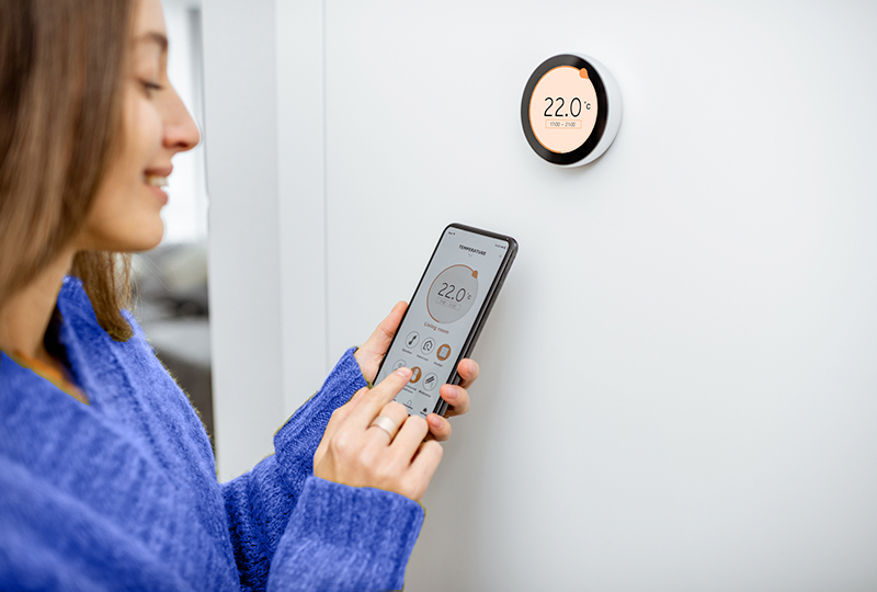 A white woman is standing next to her digital home thermostat controlling it using her smartphone