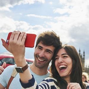 Un couple en vacances, souriant au téléphone appareil photo pour une photo