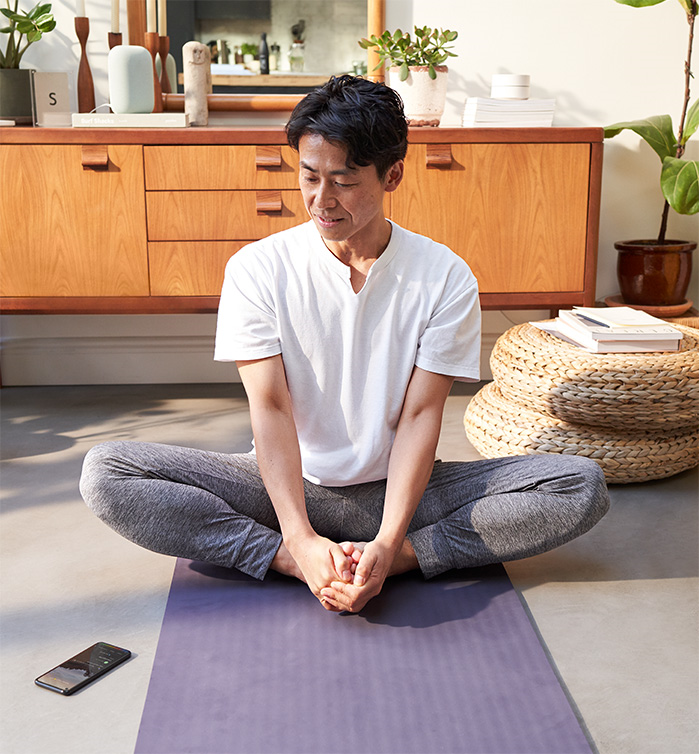 Image of a man stretching on a yoga mat while looking at his Pixel 5
