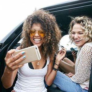 Deux femmes regardant un téléphone portable assis dans la voiture