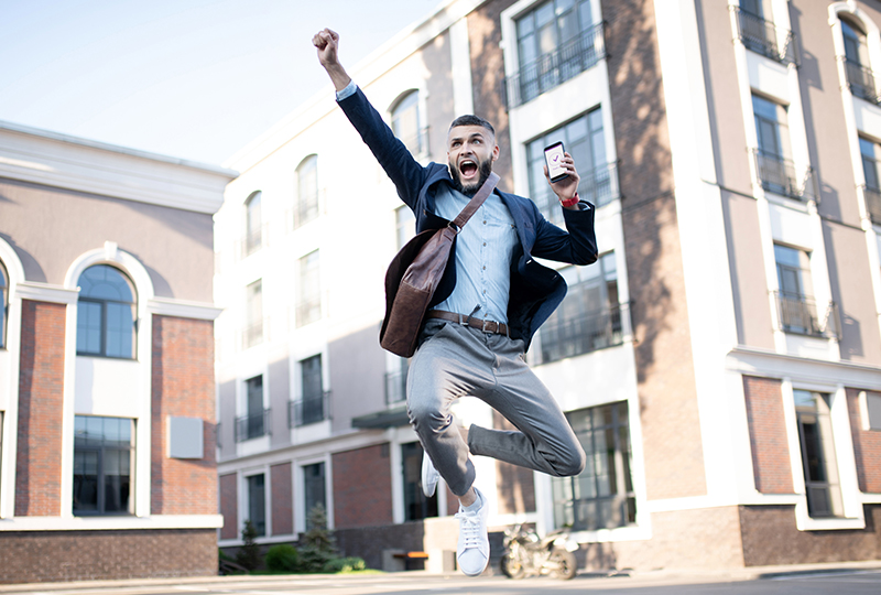 A man jumps in air with excitement, outside a building