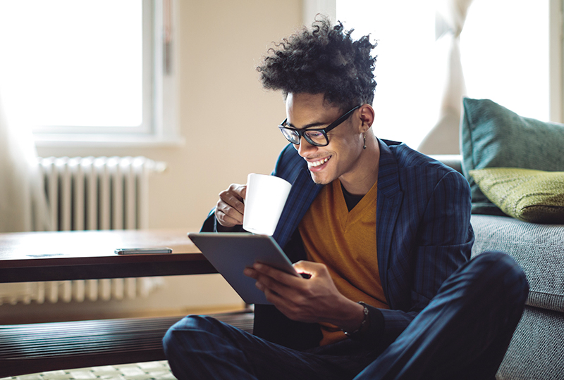 A black man scrolling through a tablet in his left hand, while holding a mug in his right hand