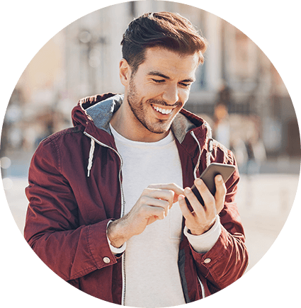 A Caucasian man wearing a hoodie smiles while he checks his phone