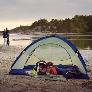 Deux enfants regardant une tablette sous une tente près d'un lac avec des parents à distance